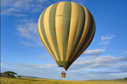 A hot air balloon floats over the Serengeti plains in Tanzania