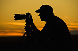 Silhouette of photographer with camera at sunset