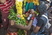 Thaipusam devotee gives holy prasad sweet to a baby