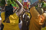 Thaipusam pilgrims slowly approach the Batu Caves with sacred burdens