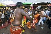 Two Thaipusam pilgrims dance in the street near the Batu Caves