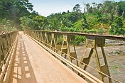 A steel Bailey bridge crosses the Ogooue River amidst jungle and plantations.