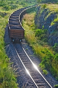A heavily laden coal train rounds a corner at sunset in Lope National Park.