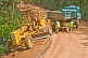 A heavy truck helps to pull a stranded grader out of trouble on a jungle logging road.