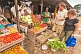 Two Western travellers buy vegetables at a market stall.