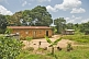 Mud-brick house with corrugated iron roof in jungle clearing.