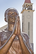 Bronze painted statue of woman praying in front of the white stucco Roman Catholic church.