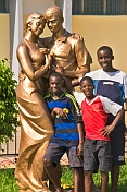 Three boys in football shirts stand in front of gold painted statue of dancing couple.