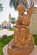 Golden statue of angel playing music in front of the white stucco Roman Catholic church.