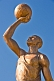 Bronze painted statue of footballer holding a ball above his head.