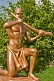 Image of Bronze painted statue of man in loincloth holding a tusk of ivory.