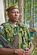 Image of An Angolan soldier with assault rifle in eucalyptus plantation.
