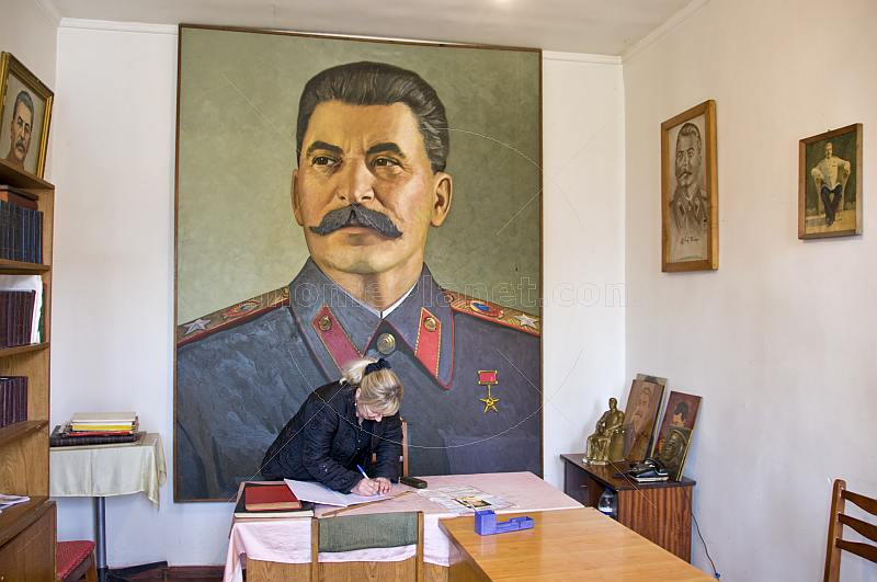 The Director of the Joseph Stalin museum prepares the visitors book in front of a huge portrait of Uncle Joe.
