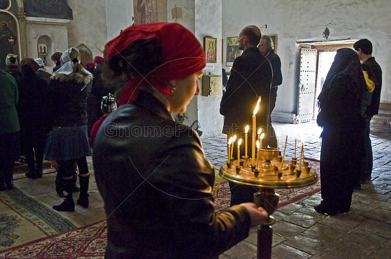A woman lights a candle during mass at the Ananuri Monastery.