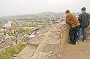 Two men gaze at the view over central Tbilisi from the ramparts of the Narikala Fortress.