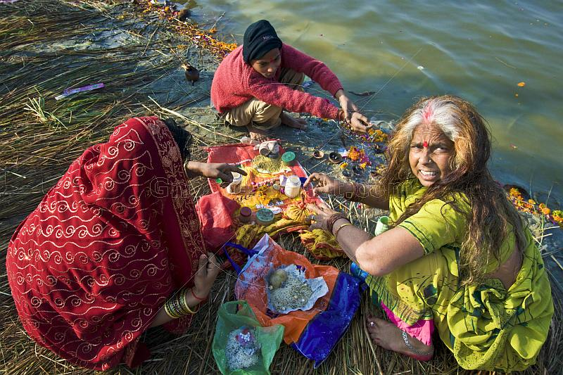 Two women and small boy prepare offerings for Hindu ceremony on Ganges River banks.