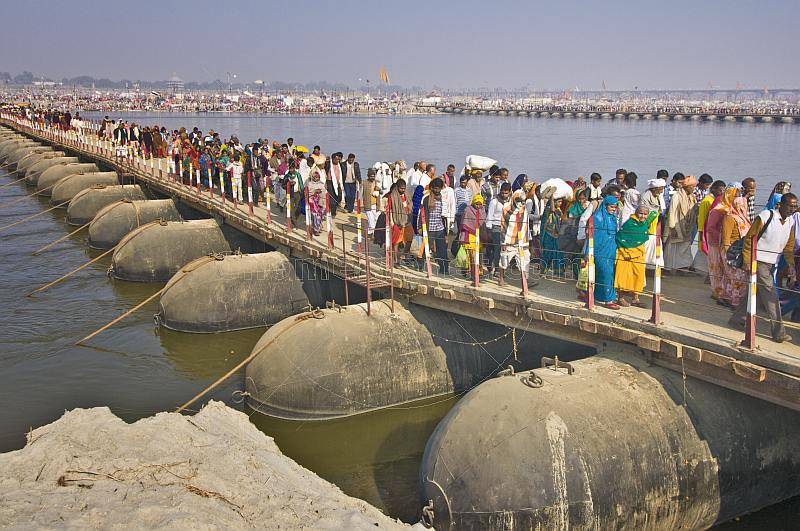 Mass crowds of Indian Hindu pilgrims cross pontoon bridge over Ganges river.