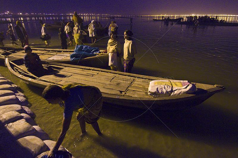 Rowing boats next to pontoon bridge 18 at Ganges Yamuna Sangam in pre-dawn light.