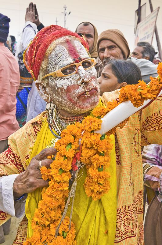 Hindu holy man with whitened face and nose ring poses for the camera.