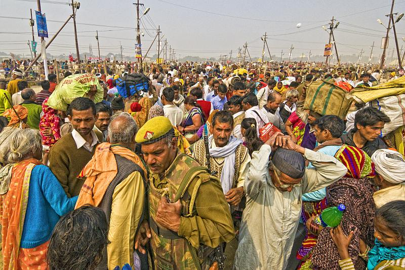 Policeman in body armor struggles through dense crowds in Kumbh Mela procession.