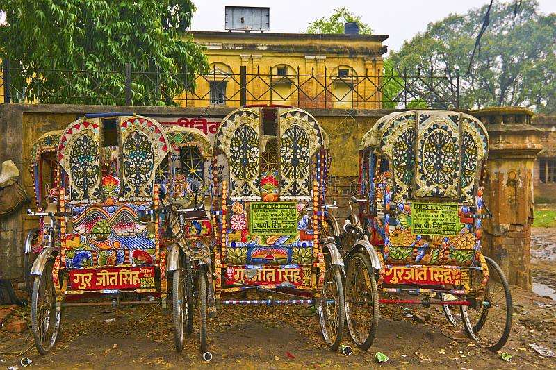 Three colorful decorated bicycle rickshaws next to old city wall.