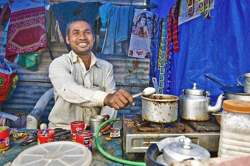 Smiling tea-stall owner adds sugar to pan of boiling Indian chai tea.