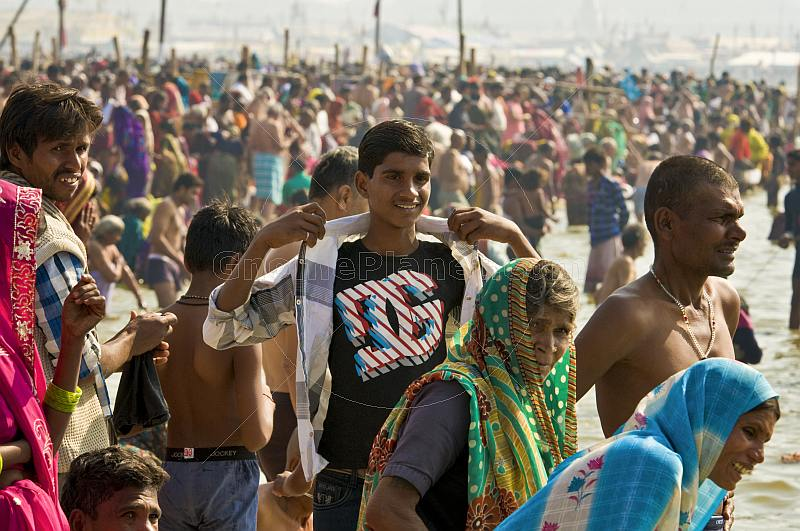 Young man with Dolce and Gabana teeshirt at crowded Ganges Sangam bathing ghats.