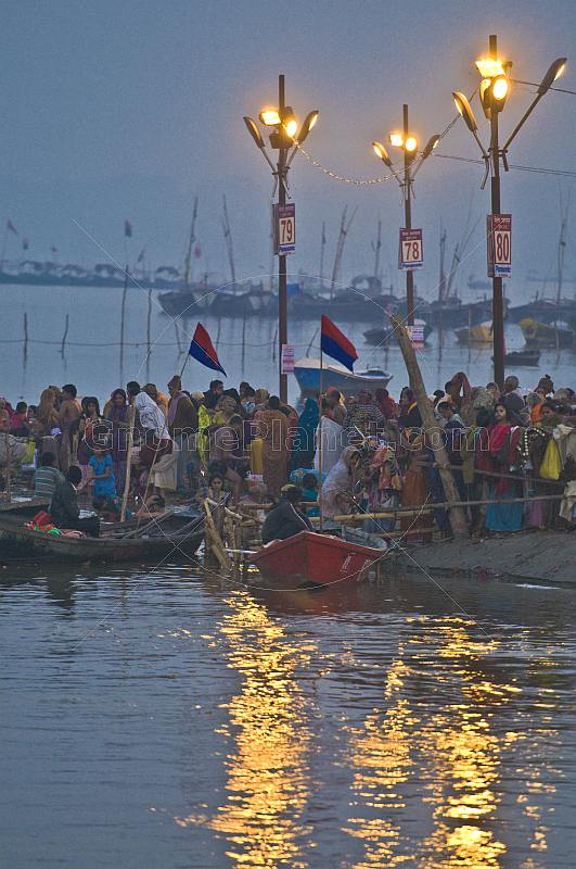 Pilgrims bathe in crowded Ganges Yamuna River Sangam area before dawn.