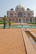 Indian father with young daughter takes a photograph of Humayun's Tomb.