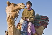 A young camel-driver enjoys an early morning cup of tea.