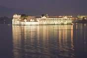 Floodlights illuminate the Lake Palace Hotel on Lake Pichola at dusk.