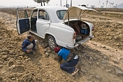 Two motorists perform some emergency repairs on an Ambassador car, fallen prey to the rough rocky roads of Bihar, near Gaya.