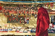 A Tibetan monk looks at Buddhist religious trinkets for sale.