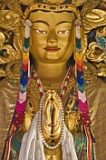 Buddhist statue in colorful robes and jewels at the Bhutanese Temple.