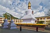 Buddhist monks walk around the gold-topped Do-drul Chorten, which contains relics and a full set of holy texts.
