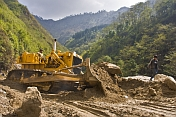 An Indian Army bulldozer deals with a sudden landslide that is blocking a mountain road.