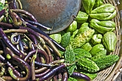A vegetable-sellers basket of purple eggplants and green bitter-gourds.