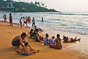 Indian families play in the waves on Leela Beach at sunset.