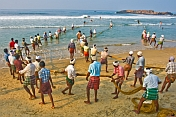 Fishermen struggle to haul their fishing net through the surf and on to the beach.