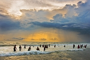 India, Kerala, Kovalam. Indian bathers play in the surf during a cloudy sunset.