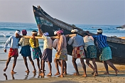 Fishermen strain to launch their fishing boat into the surf.