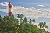 Red and white bands of Vizhinjam Lighthouse tower, set amongst coconut palm trees.