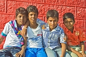 Four Indian schoolboys in colored shirts pose for their photograph.