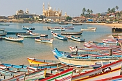Boats at anchor in Vizhinjam fishing harbour, with mosque in the distance.