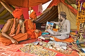 Juna Akhara Naga shows Guru picture to two Sadhus.