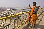 Hindu Sadhu takes photo of Kumbh Mela tents from Lal Bahadur Shastri Bridge.