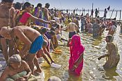 Mass crowds of Hindu pilgrims struggle to bathe in shallows of Ganges river Sangam.