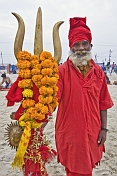 Hindu Holy Man Dressed In Red With Marigold Decorated Brass Trident