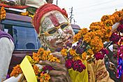 Hindu holy man with whitened face and orange glasses poses for the camera.