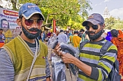 Two Young Men Sell False Beards and Moustaches To Kumbh Mela Visitors
